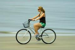 Muchacha que monta una bici en la playa Fotos de archivo