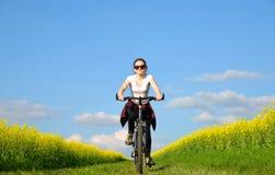 Muchacha que monta una bici en un camino de tierra Fotografía de archivo