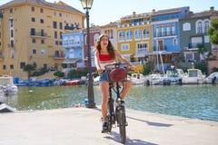 Muchacha que monta una e-bici plegable en un puerto fotos de archivo