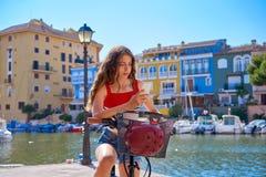 Muchacha que monta una e-bici plegable en un puerto deportivo mediterráneo foto de archivo