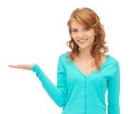 Muchacha que muestra algo en la palma de su mano Fotografía de archivo libre de regalías