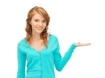 Muchacha que muestra algo en la palma de su mano Imágenes de archivo libres de regalías