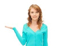 Muchacha que muestra algo en la palma de su mano Imagen de archivo libre de regalías