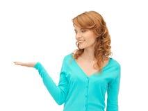 Muchacha que muestra algo en la palma de su mano Imagen de archivo