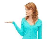 Muchacha que muestra algo en la palma de su mano Foto de archivo
