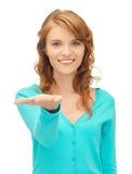 Muchacha que muestra algo en la palma de su mano Fotografía de archivo