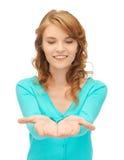 Muchacha que muestra algo en las palmas de sus manos Fotografía de archivo libre de regalías