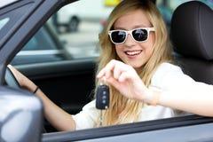 Muchacha que muestra clave del coche Fotografía de archivo libre de regalías
