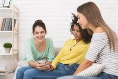 Muchacha que muestra el vídeo divertido en smartphone a los amigos imagen de archivo