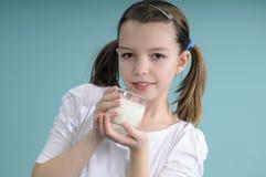 Muchacha que muestra el vidrio con leche Imagen de archivo libre de regalías