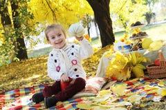 Muchacha que muestra la calabaza hecha a mano debajo de árboles del otoño Fotografía de archivo libre de regalías