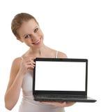 Muchacha que muestra la computadora portátil con la pantalla vacía del espacio Fotos de archivo libres de regalías