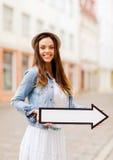 Muchacha que muestra la dirección con la flecha en la ciudad Fotografía de archivo libre de regalías