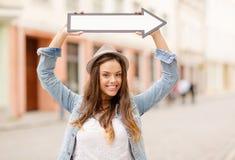 Muchacha que muestra la dirección con la flecha en la ciudad Foto de archivo libre de regalías