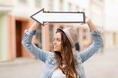 Muchacha que muestra la dirección con la flecha en la ciudad Imágenes de archivo libres de regalías