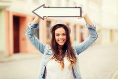 Muchacha que muestra la dirección con la flecha en la ciudad Fotos de archivo libres de regalías