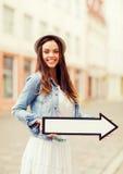 Muchacha que muestra la dirección con la flecha en la ciudad Foto de archivo
