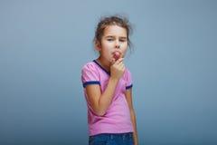 Muchacha que muestra la lengua en un fondo gris Foto de archivo