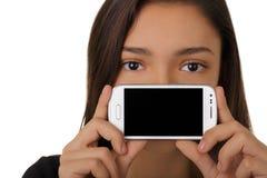 Muchacha que muestra la pantalla elegante del teléfono imagen de archivo