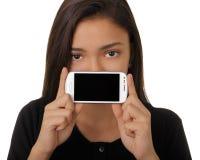 Muchacha que muestra la pantalla elegante del teléfono foto de archivo