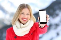 Muchacha que muestra la pantalla en blanco del teléfono en una montaña nevosa Imagenes de archivo
