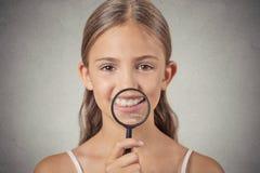 Muchacha que muestra los dientes a través de una lupa Imágenes de archivo libres de regalías