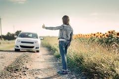 Muchacha que muestra los pulgares hasta un coche que pasa el camino Imagen de archivo libre de regalías
