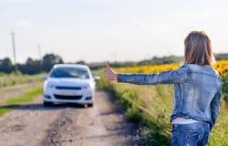 Muchacha que muestra los pulgares hasta un coche que pasa el camino Fotografía de archivo
