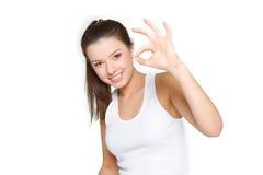 Muchacha que muestra OK sobre blanco Fotografía de archivo libre de regalías