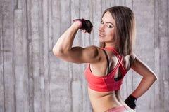 Muchacha que muestra sus músculos Foto de archivo libre de regalías