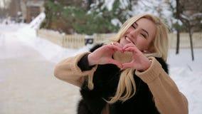 Muchacha que muestra un símbolo del corazón por las manos en el invierno almacen de video