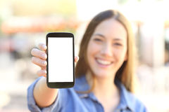 Muchacha que muestra una exhibición elegante en blanco del teléfono Fotografía de archivo