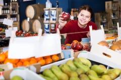 Muchacha que muestra una manzana roja jugosa Foto de archivo libre de regalías