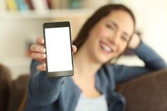 Muchacha que muestra una pantalla en blanco del smartphone a la cámara Imagenes de archivo