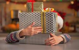 Muchacha que oculta detrás de la pila de cajas del regalo de Navidad Imagen de archivo libre de regalías