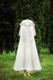 Muchacha que oculta detrás de su vestido de boda largo imagen de archivo libre de regalías