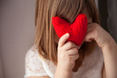 Muchacha que oculta detrás de un corazón rojo hecho punto, el día de tarjeta del día de San Valentín, timidez Fotos de archivo