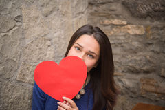 Muchacha que oculta detrás de una muestra bajo la forma de corazón Imágenes de archivo libres de regalías