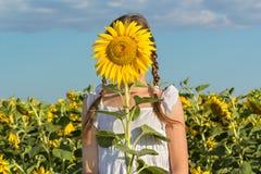 Muchacha que oculta detrás del girasol de la flor Imágenes de archivo libres de regalías