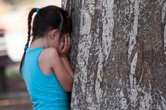 Muchacha que oculta o que llora cerca de un árbol Fotos de archivo