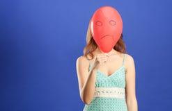 Muchacha que oculta sobre el globo enojado rojo imagenes de archivo