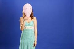 Muchacha que oculta sobre el globo sorprendido rosado fotografía de archivo