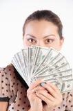 muchacha que oculta su cara detrás de un dinero Imagen de archivo libre de regalías