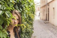 Muchacha que oculta su cara en los verdes en la calle Imagen de archivo libre de regalías