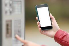 Muchacha que paga con un teléfono elegante y que muestra la pantalla Imagen de archivo libre de regalías