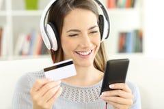 Muchacha que paga música en línea con la tarjeta de crédito Fotos de archivo libres de regalías