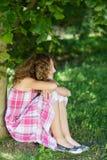 Muchacha que parece ausente mientras que se sienta en parque Fotos de archivo libres de regalías