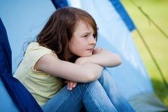 Muchacha que parece ausente mientras que se sienta en tienda Fotos de archivo
