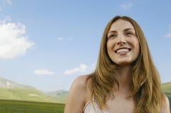 Muchacha que parece ausente mientras que sonríe en el parque Foto de archivo libre de regalías