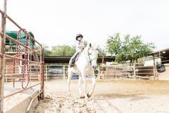 Muchacha que participa en programa equino de la terapia foto de archivo libre de regalías